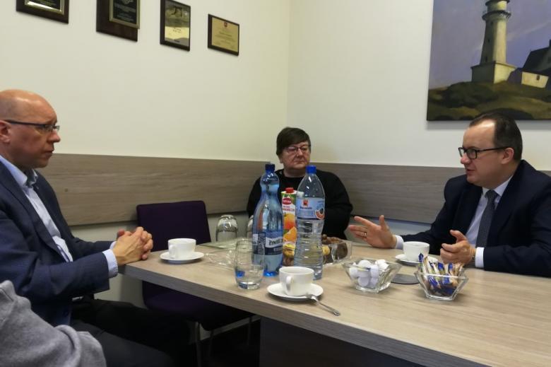 Dwaj męzczyźni i kobieta rozmawiają przy stole