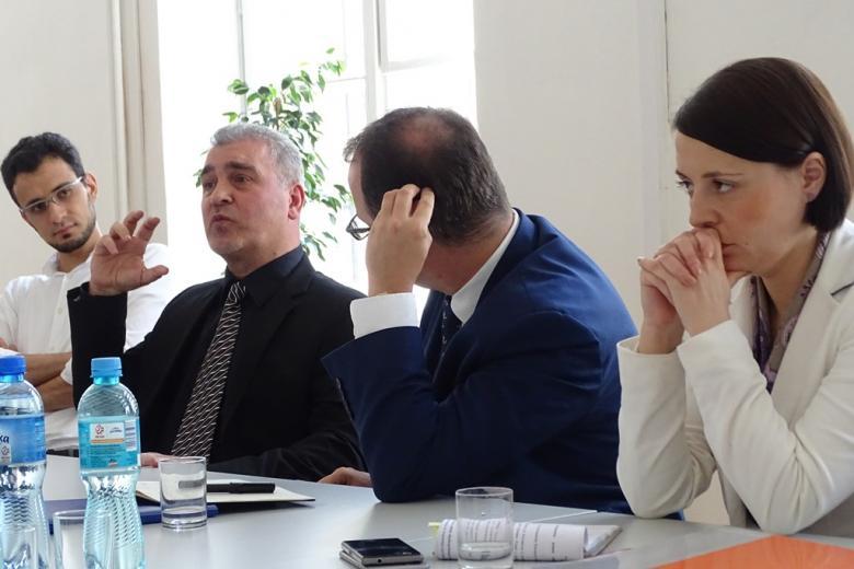 Zdjęcie: mężczyzna mówi gestykulując. Pozostali słuchają