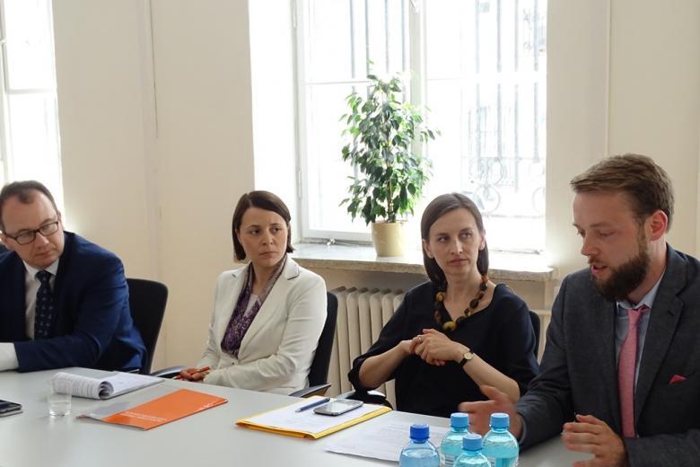 Zdjęcie: młody mężczyzna zabiera głos, dwie kobiety i mezczyzna słuchają