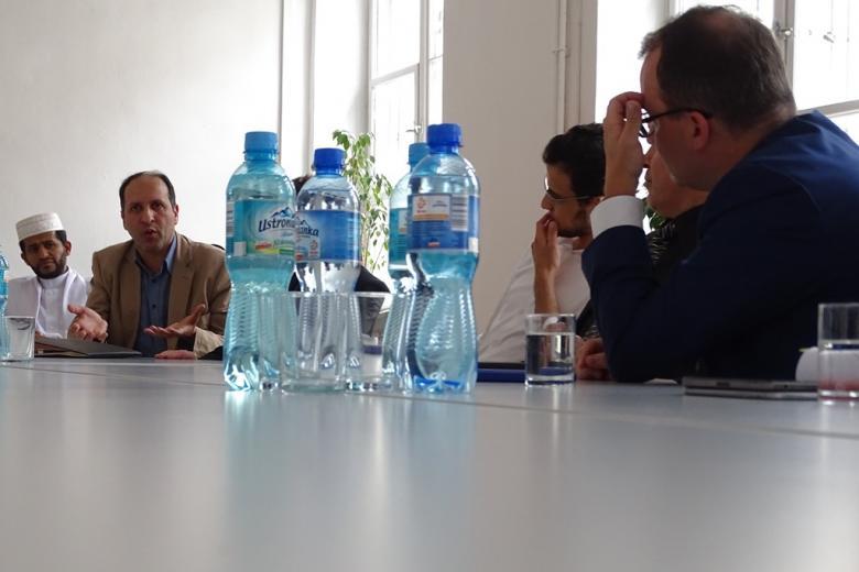 Zdjęcie: ludzie przy stole, na którym stoi woda mineralna, w gorącej dyskusji