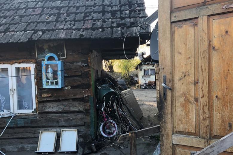 Drewniany dom w złym stanie z figurą Matki Boskiej