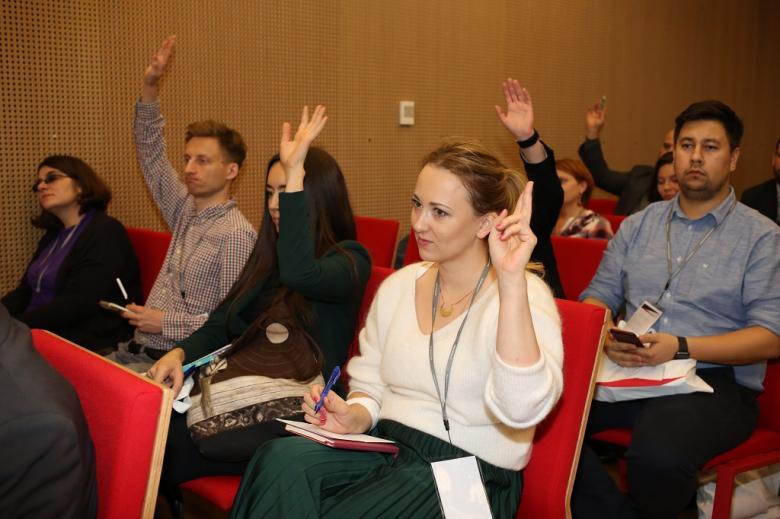 Uczestnicy panelu podnoszą ręce, czerwone krzesła