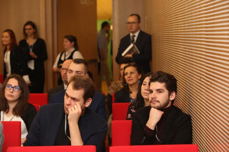 Ludzie na sali, Adam Bodnar stoi w rogu i przysłuchuje się debacie