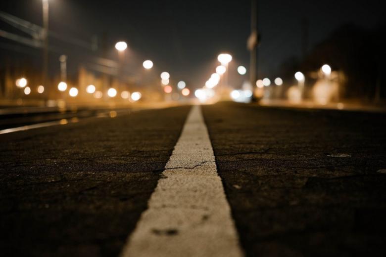 Ulica nocą, biała linia dzieląca jezdnie