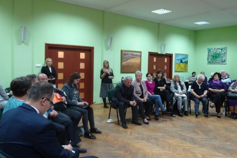 Zdjęcie: ludzie siedzą, kobieta stoi