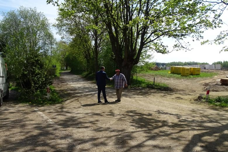 Dwaj mężczyźni na drodze witają się. jeden w roboczym ubraniu, drugi - w garniturze