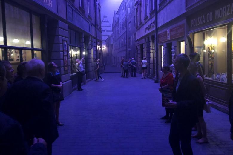 Ludzie w ciemnym pomieszczeniu, którego scenografia przypomina przedwojenną ulicę
