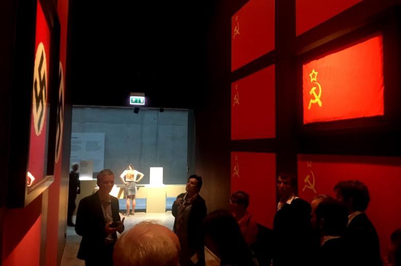 Ludzie na sali wystawowej - w wąskim pomieszczeniu na ścianie z jednej strony wiszą hitlerowskie swastyki, z drugiej - symbole komunistyczne