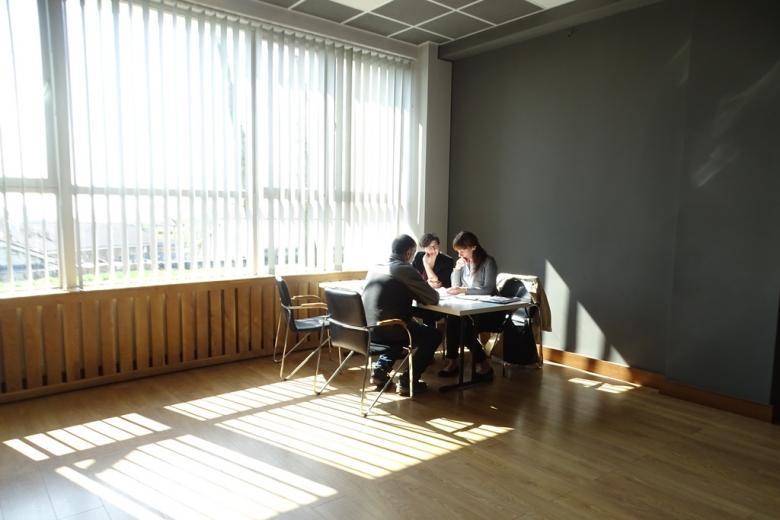 Trzy osoby przy stoliku oświetlonym przez słońce