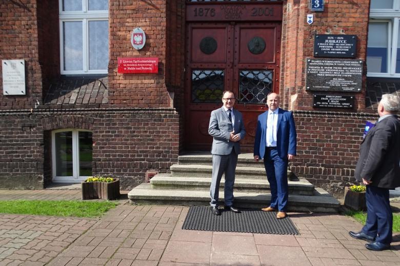 Dwaj męzczyźni przed starym ceglanym budynkiem