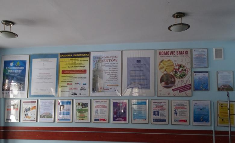 Plakaty i dyplomy na ścianie
