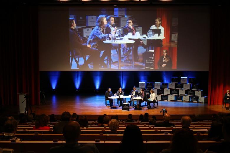 Widok na audytorium od tylu: paneliści na scenie i publiczność