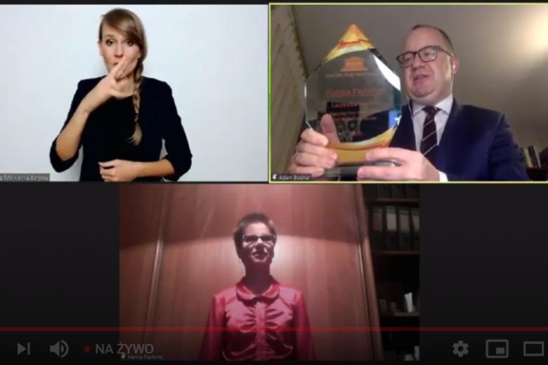 mężczyzna prezentuje szklaną statuetkę do kamery, tłumaczka migowa i elegancka kobieta w okularach