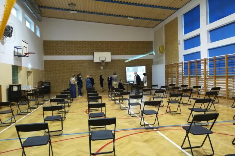 Mała grupa ludzi na sali gimnastycznej, na której stoją puste krzesła