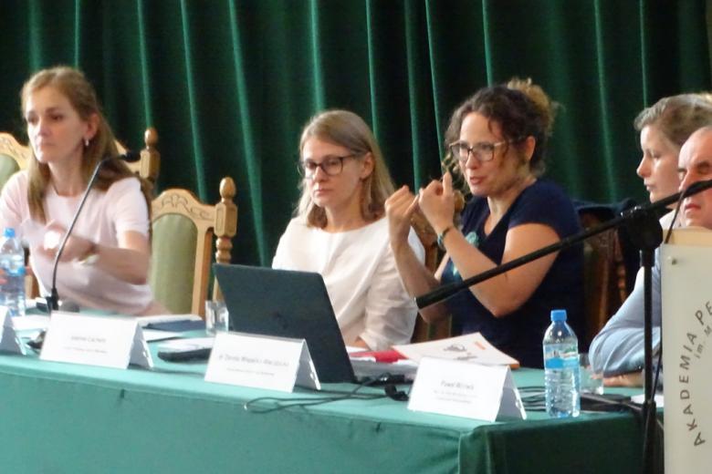 Paneliści przy stole., kobieta mówi gestykulując