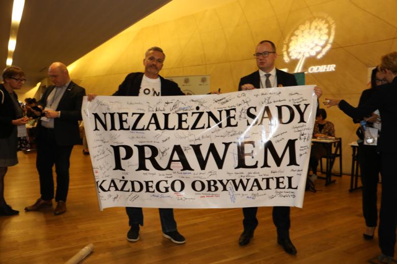 """Dwaj mężczyźni trzymają transparent """"Niezależne sądy prawem"""""""