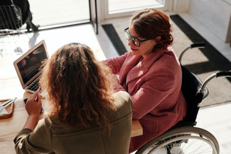 dwie osoby przy komputerze, jedna z nich niepełnosprawna