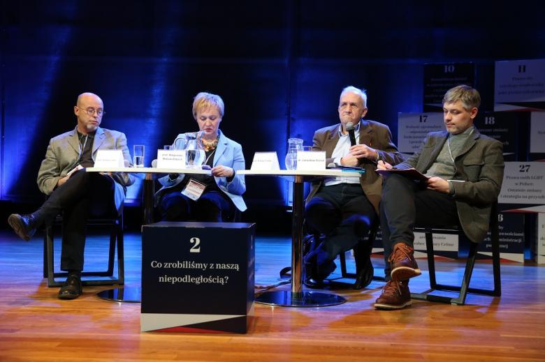 Paneliści na scenie. Przed nimi sześcian z nazwą panelu