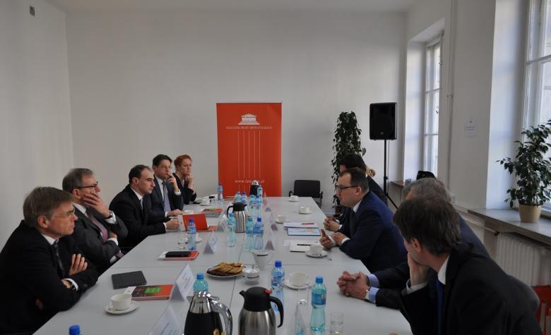 zdjęcie: po obu stronach białego stołu siedzi kilka osób