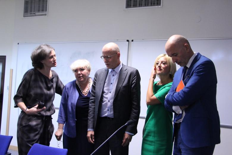 Cztery osoby  pozują do zdjęcia rozmawiając