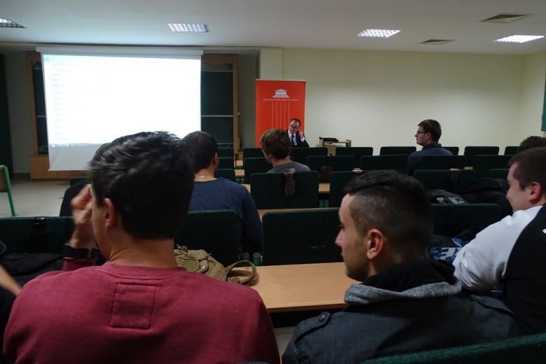 Zdjęcie: widok na salę wykładową ponad głowami dwóch młodych ludzi