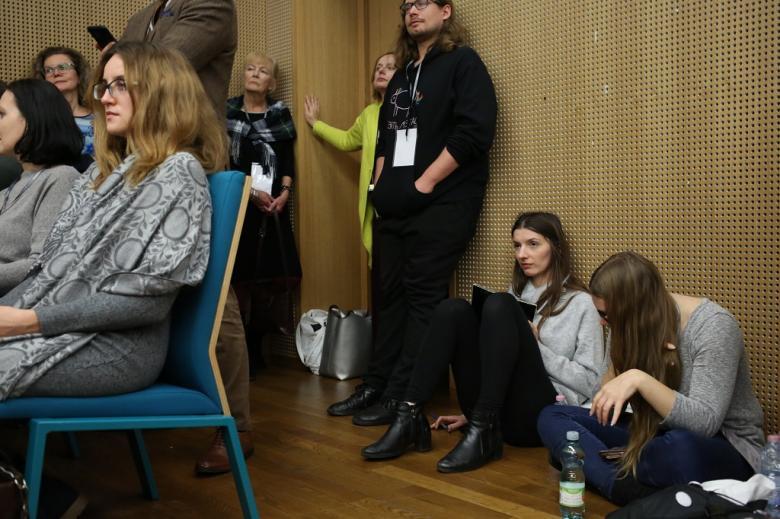 Ludzie stoją pod ścianami, jedna siedzi na podłodze