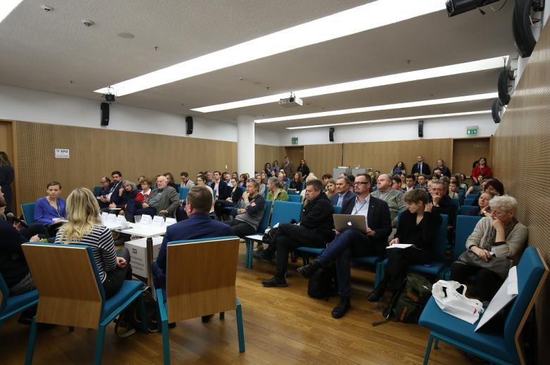 Widok na pełną salę i panelistów, zielone krzesła