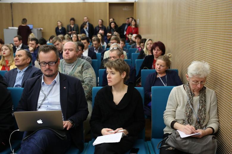 Sala pełna ludzi, na pierwszym planie mężczyzna notuje na laptopie
