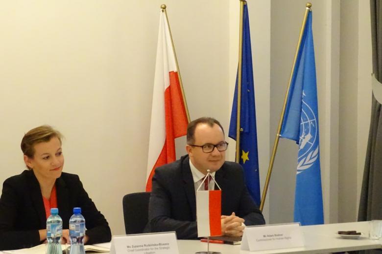 Kobieta i mężczyzna przy stole, z tyłu flagi Polski, UE i Narodów Zjednoczonych