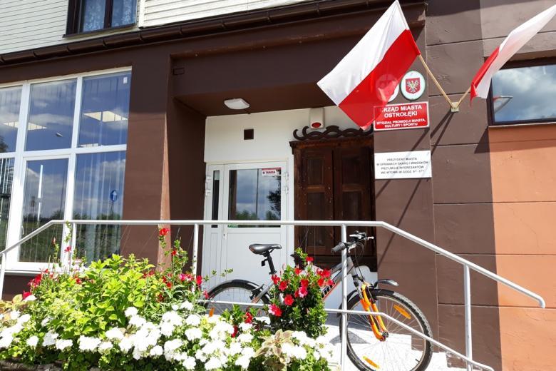 Budynek z biało-czerwoną flagą, przed nim rower
