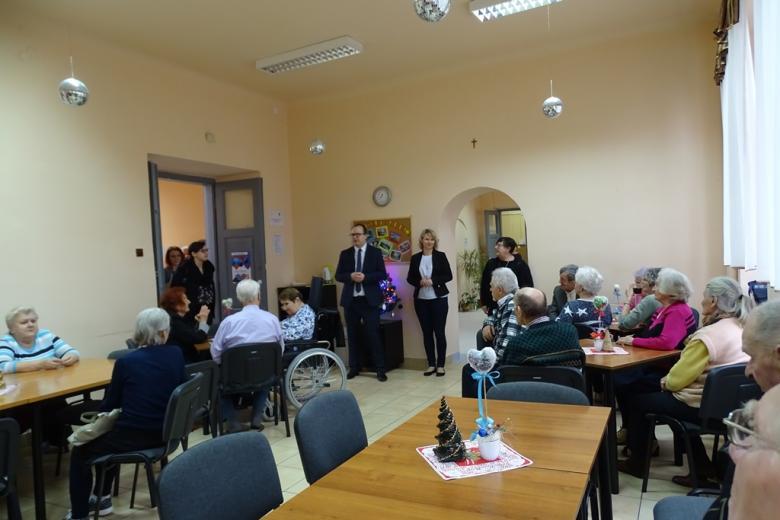 Grupa starszych osób, część na wózkach, męzczyzna stoi