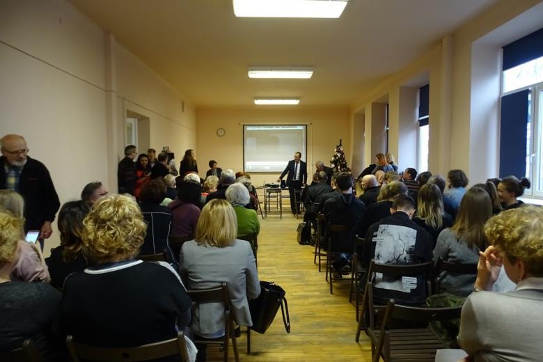 Duża grupa ludzi na sali, mężczyzna stoi