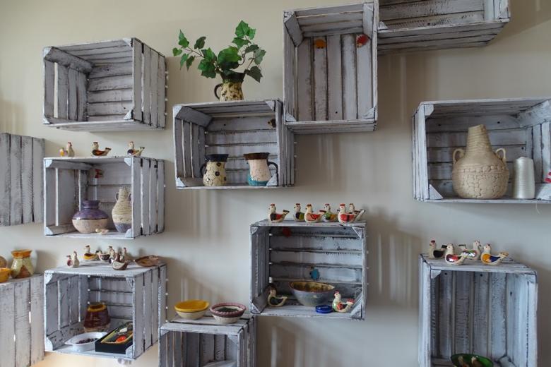 Półki zrobione ze skrzynek, w nich gliniane ozdoby