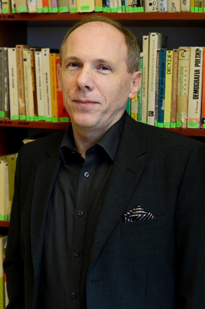 Mężczyzna w ciemnej koszuli  marynarce na tle półek z książkami