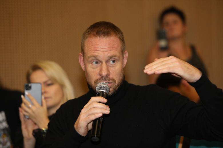 Mężczyzna w ciemnym swetrze mówi do mikrofonu