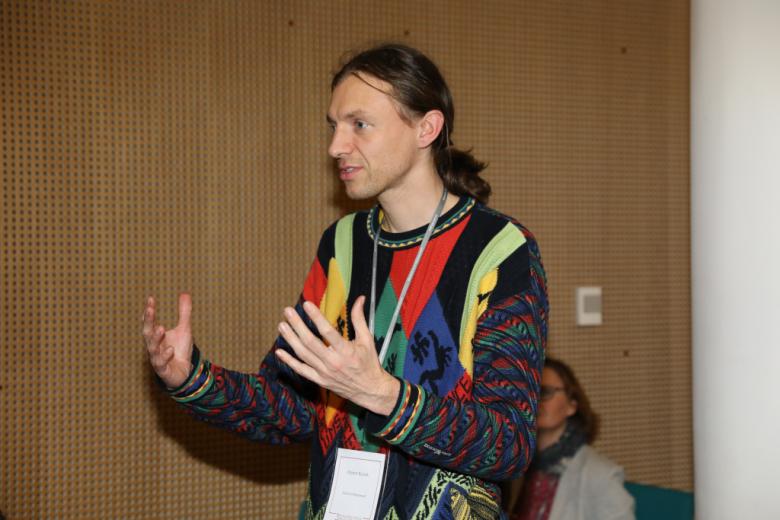Mężczyzna w kolorowym swetrze mówi