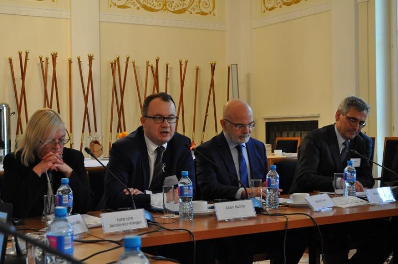 zdjęcie: za stołem od lewej strony siedzi kobieta i trzech mężczyzn