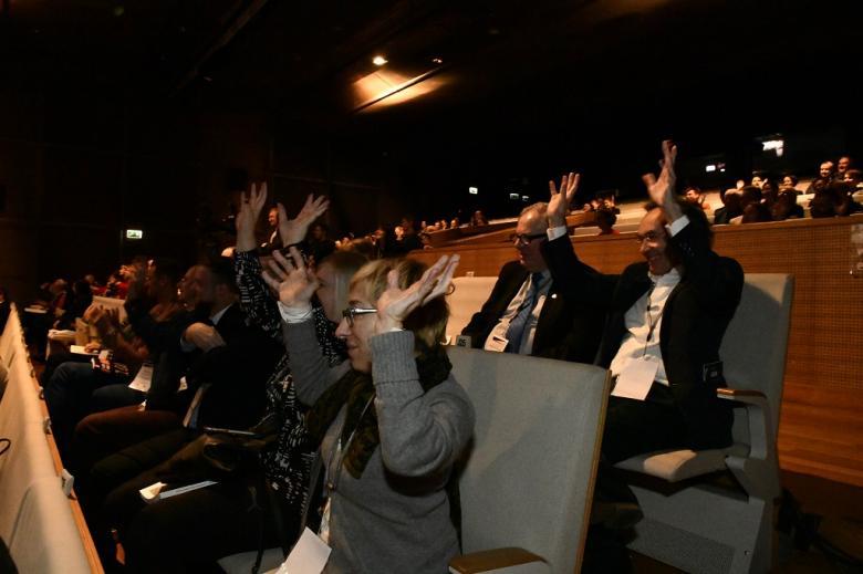 Publiczność w audytorium potrząsa podniesionymi dłońmi