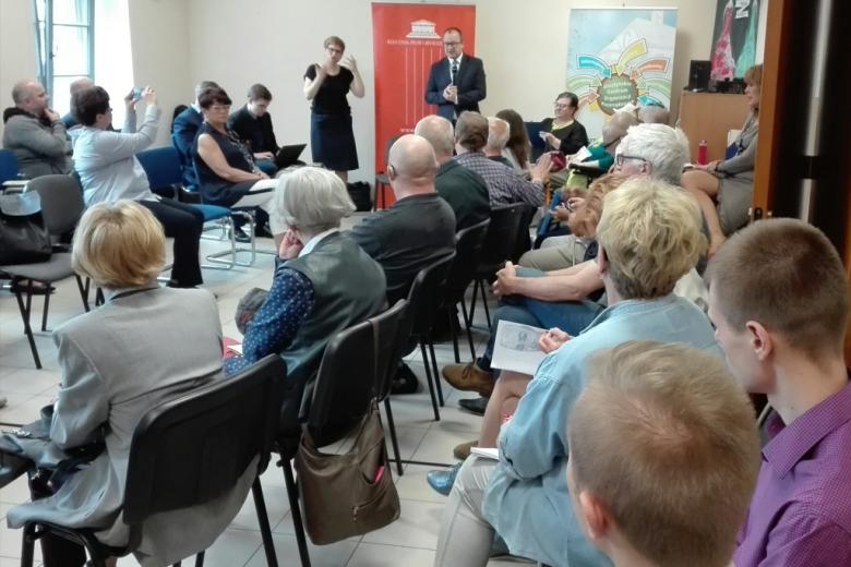 Ludzie na sali, mężczyzna stoi, tłumaczka języka migowego, roll-up Biura RPO