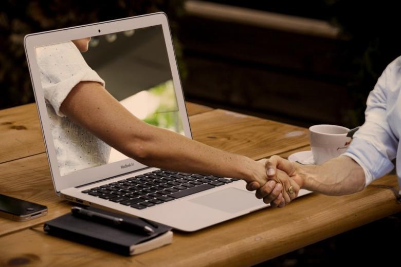 witająca się ręka wychodzi z monitora konputera