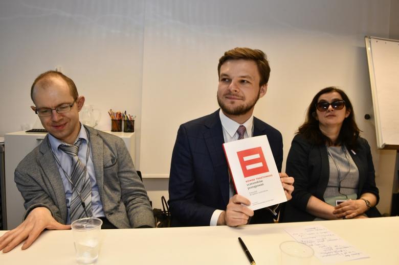 Paneliści pokazują publikację z czerwonym znakiem równości na okładce