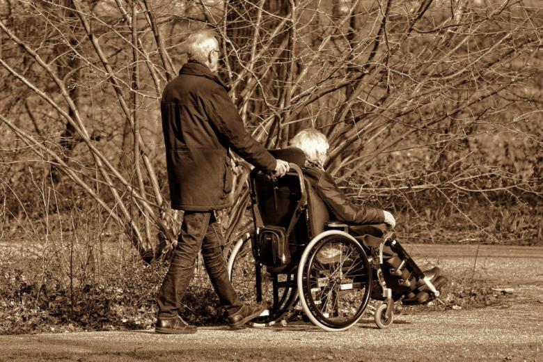 Mężczyzna pcha wózek, na którym siedzi kobieta