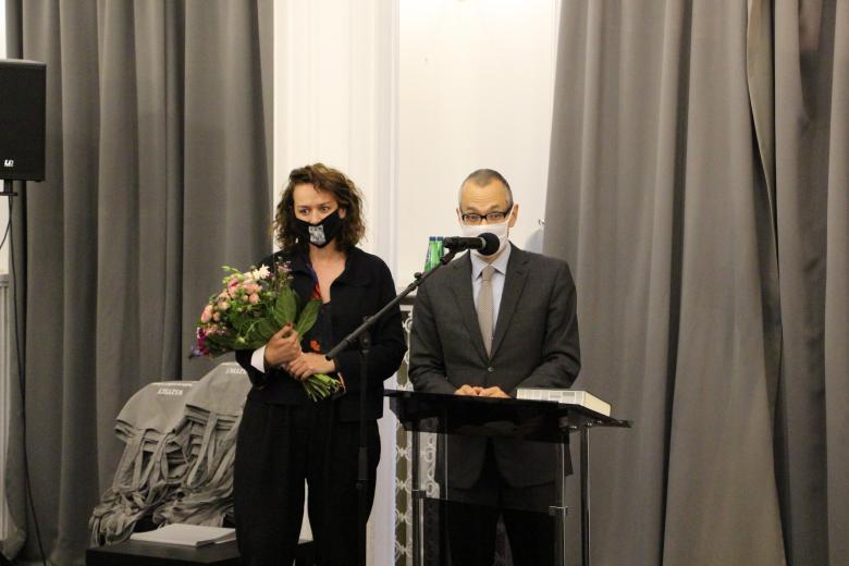 Kobieta i mężczyzna w maseczce stoją z bukietem