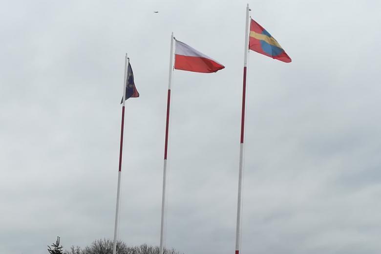Flaga polska, unijna i Ostrowa Wielkopolskiego na wysokich masztach