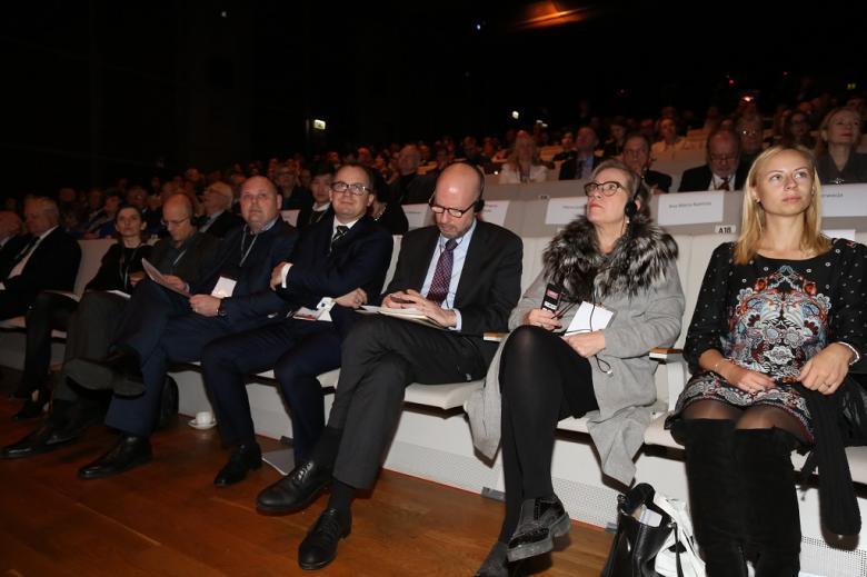 Zapełniona widownia, w pierwszym rzędzie ludzie słuchają w słuchawkach tłumaczenia wystąpień