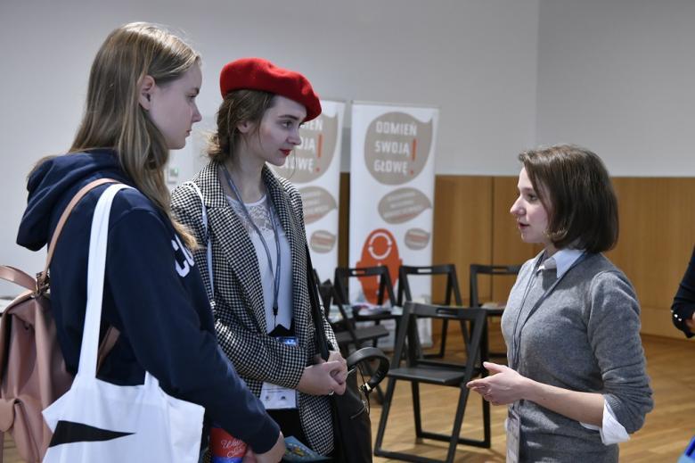 Młode kobiety rozmawiają przy rejestracji. Jedna ma wiśniowy beret