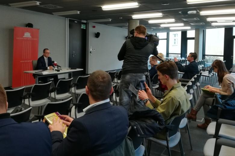 Dziennikarze i mężczyzna przy stole
