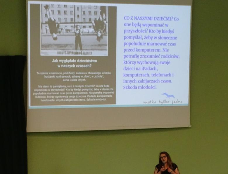 """Młoda kobieta pod slajdem, na którycj jest zdjęcie z lat 70. dzieci bawiących się na trzepaku i napis """"A co z naszymi dziećmi"""""""