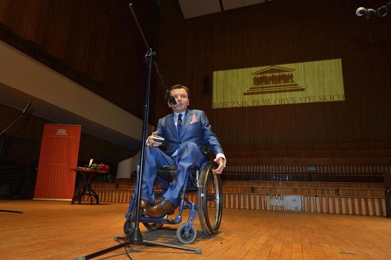 mężczyzna na wózku przed mikrofonem w tle logo RPO