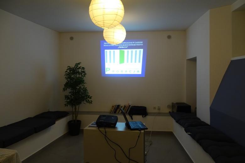 Zdjęcie: pusta sala, na ścinie prezentacja z napisem Małopolskie Stowarzyszenie Probacja